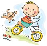 乘坐他的三轮车的男孩 免版税库存照片