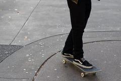 乘坐他的滑板的年轻人在胶弄脏了具体车行道 库存照片