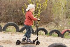 乘坐他的滑行车的小男孩在土车道 免版税库存图片