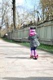 乘坐滑行车的桃红色的小女孩 库存照片