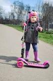 乘坐滑行车的桃红色的小女孩 免版税图库摄影
