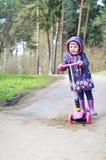 乘坐滑行车的桃红色的小女孩 库存图片