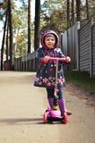 乘坐滑行车的桃红色的小女孩 免版税库存照片