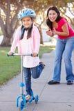 乘坐滑行车的母亲教的女儿 免版税库存图片
