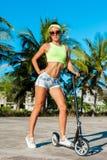 乘坐滑行车的被晒黑的妇女全长画象在棕榈附近在热带国家 库存图片