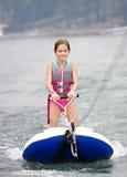 乘坐滑雪管的女孩在小船后 免版税库存照片