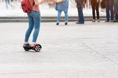 乘坐hoverboard的少妇在城市广场 新的运动和运输技术 关闭双重轮子自已 免版税库存照片