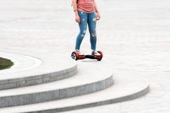 乘坐hoverboard的少妇在城市广场 新的运动和运输技术 关闭双重轮子自已 免版税图库摄影