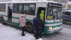 乘客上在公共交通工具的-在大雪冬天风暴期间的商业城市公共汽车 股票视频