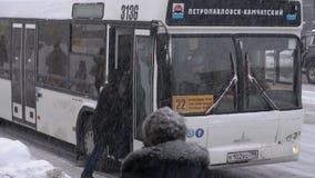 乘客上在公共交通工具的-在暴风雪飞雪期间的商业城市公共汽车 股票视频
