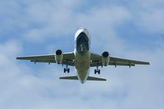 乘客与云彩和蓝天的飞机着陆 免版税图库摄影