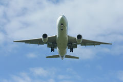 乘客与云彩和蓝天的飞机着陆 免版税库存照片