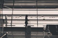 乘客与在机场终端继续等待延迟飞行的行李在门 免版税库存图片