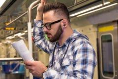 乘客人是一热忱的大学生看书,当乘坐在家乘地铁时 集中的概念, 库存照片