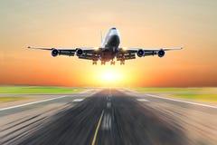 乘客在一条跑道的飞机着陆在明亮的红色日落期间的晚上 图库摄影