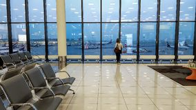 乘客在国际机场等待飞机,看法通过窗口,旅行概念 免版税库存图片