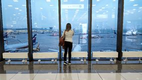 乘客在国际机场等待飞机,看法通过窗口,旅行概念 免版税库存照片
