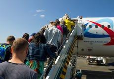 乘客在多莫杰多沃机场爬在航空公司乌拉尔航空公司飞机上的梯子  免版税库存照片