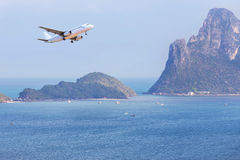 乘客在小海岛上的飞机着陆蓝色海和热带海滩的 库存图片