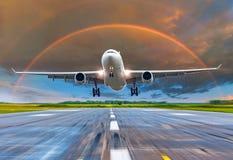 乘客在日落彩虹的飞机着陆在跑道 库存照片