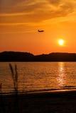 乘客在日落的飞机着陆剪影  免版税图库摄影