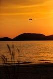 乘客在日落的飞机着陆剪影  免版税库存照片