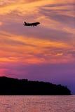 乘客在日落的飞机着陆剪影  免版税库存图片