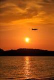 乘客在日落的飞机着陆剪影  库存图片