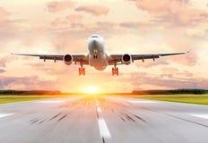 乘客在日落的飞机着陆在跑道 免版税库存照片