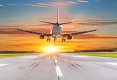 乘客在日落的飞机着陆在跑道 图库摄影