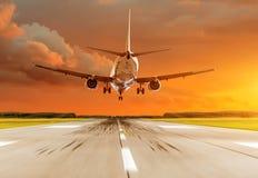 乘客在日落的飞机着陆在跑道 免版税库存图片