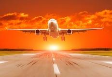 乘客在日落的飞机着陆在跑道 库存照片