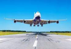 乘客在清楚的蓝天的飞机着陆在跑道 库存图片