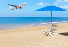 乘客在热带海滩上的飞机着陆与白色木海滩睡椅和蓝色遮阳伞 库存图片