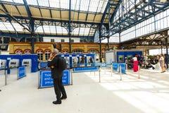 乘客在自助出纳员的购买票在布赖顿火车站,英国 库存照片