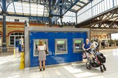 乘客在自助出纳员的购买票在布赖顿火车站,英国 图库摄影