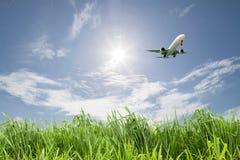 乘客在蓝天背景的飞机着陆 库存照片