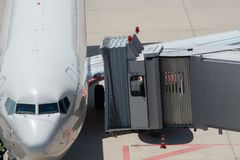 乘客在飞机上靠码头的搭乘桥梁 图库摄影