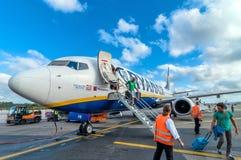 乘客在登陆以后下飞机瑞安航空公司喷气机飞机在比萨机场,意大利 免版税库存图片