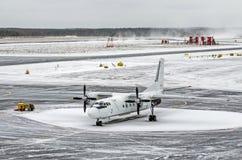 乘客小飞机在机场在坏雪的冬天和飞雪风化 图库摄影