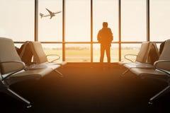 乘客座位在离开休息室为看见飞机,从机场终端的看法 运输旅行conceptt 免版税库存照片
