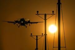 乘客接近跑道的螺旋桨推进式飞机在日落 图库摄影