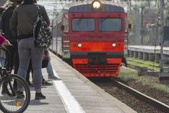 乘客期待在驻地的平台的到达的火车 库存照片