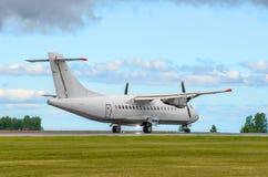 乘客涡轮螺旋桨发动机飞机着陆反对蓝天的跑道 免版税库存照片