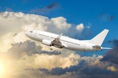 乘客白色飞机离开反对积云背景在日落 免版税库存图片