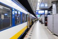乘客站立靠近火车在斯希普霍尔火车站 免版税库存图片