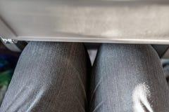 乘客腿碰到在便宜的民航的后座 人膝盖的狭窄的空间在预算载体飞机 便宜地 库存照片