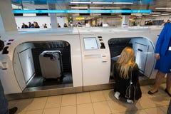 乘客采取她的行李到机器 免版税图库摄影