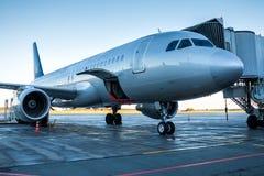 乘客飞机停放对有开放行李的一座搭乘桥梁 免版税库存图片