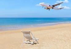 乘客飞机在热带海滩上的飞行着陆与白色木海滩睡椅 免版税库存图片